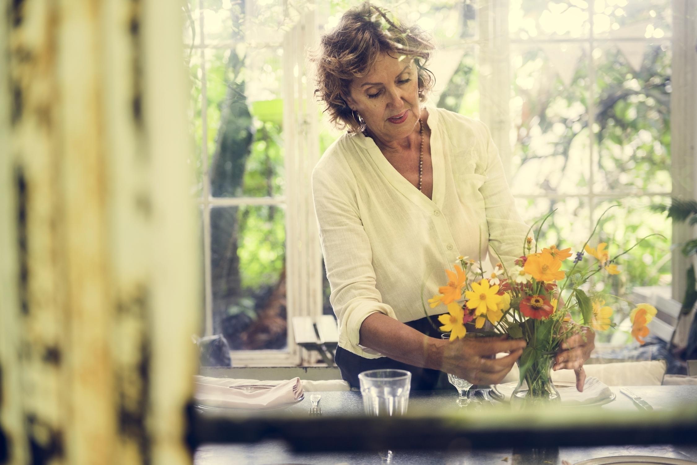 mujer-colocando-flores-sobre-la-mesa-en-jarrón-hogar-sostenible-o-ecologico
