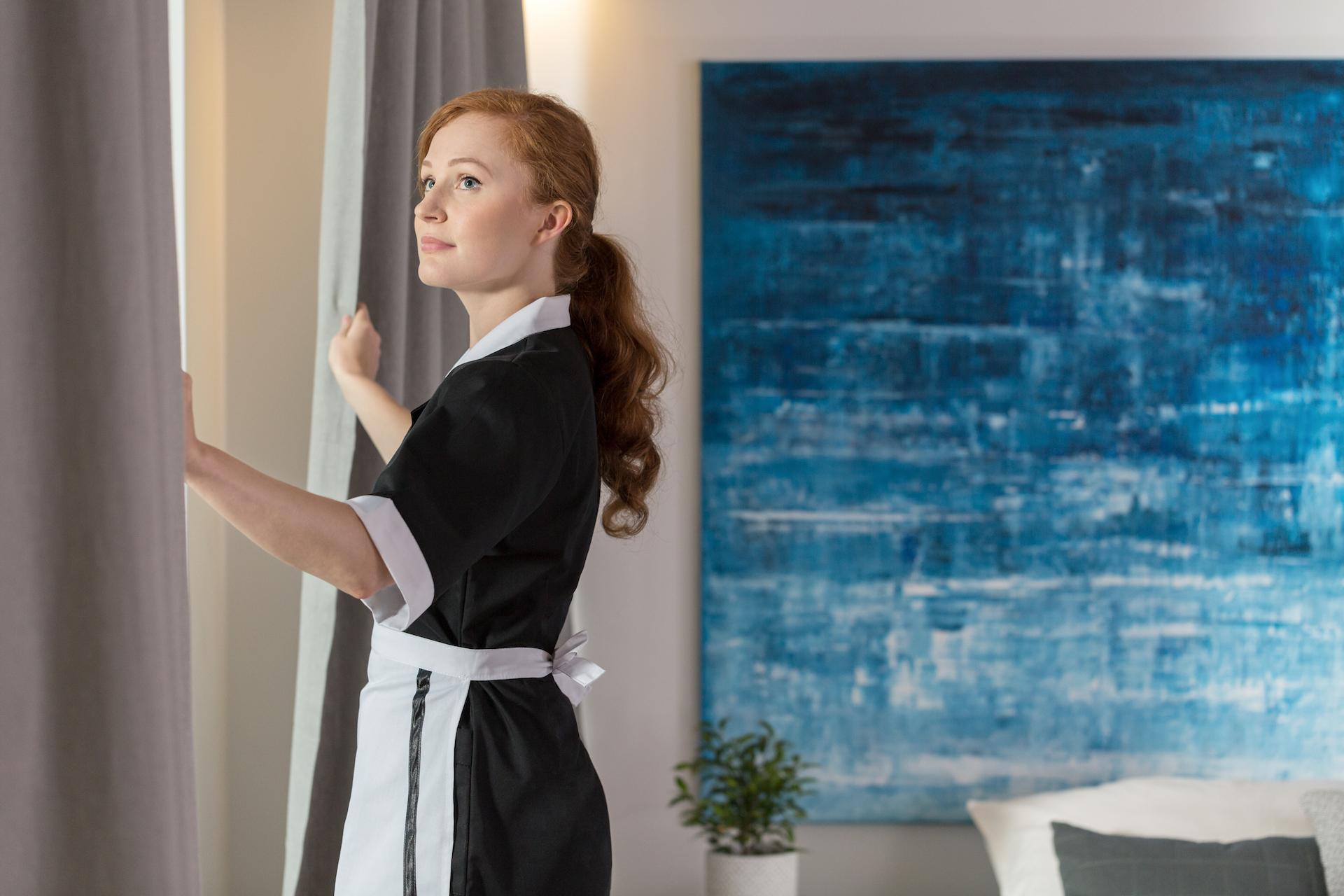 mujer-vestida-de-uniforme-de-limpieza-abre-cortinas en-ventana