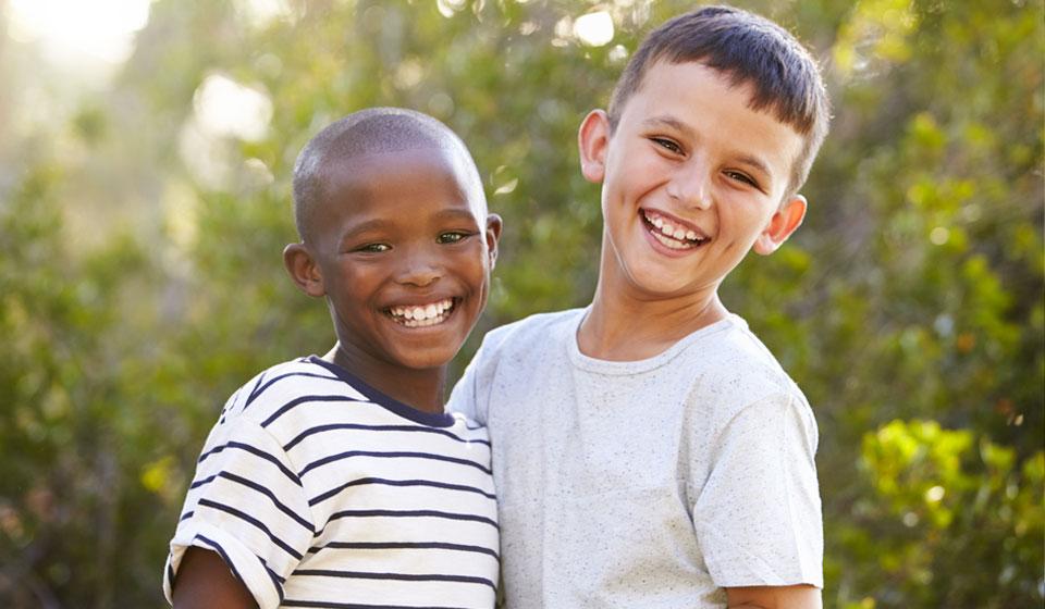 niño-de-raza-blanc-y-niño-de-raza-negra-sonrientes-y-juntos-mirando-a-la-camara